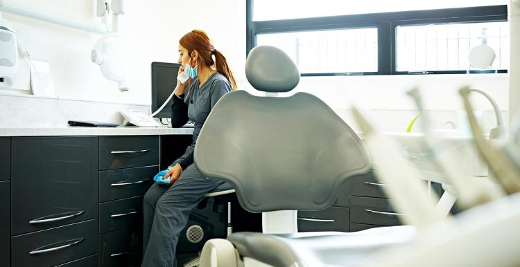 Female dentist sitting at her desk in medical room talking on telephone