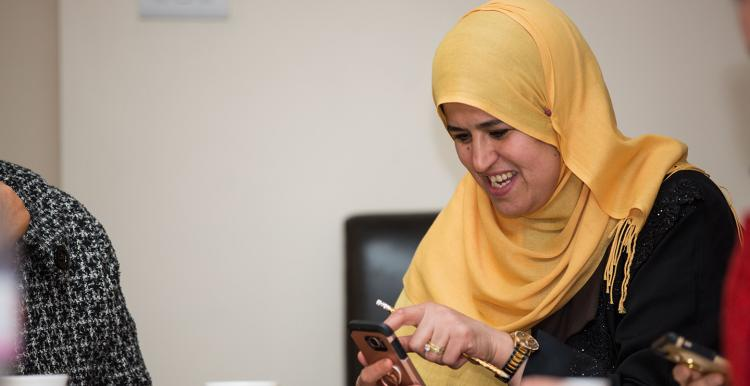 Woman in head scarf learning about her smartphone at a digital inclusion event