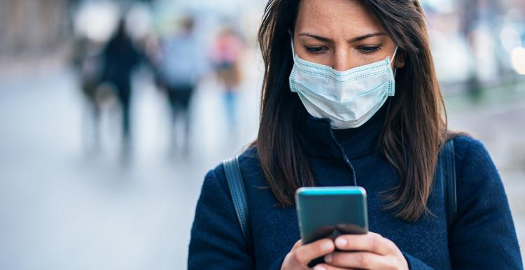 Woman wearing a facemask and looking at her smartphone