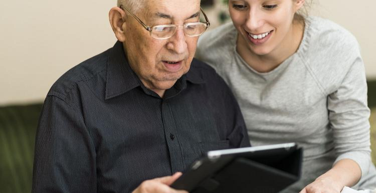 Older man and younger woman looking at a tablet