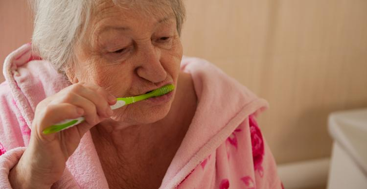 Elderly woman brushing her teeth