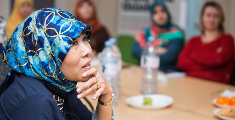 A woman in a headscarf listening