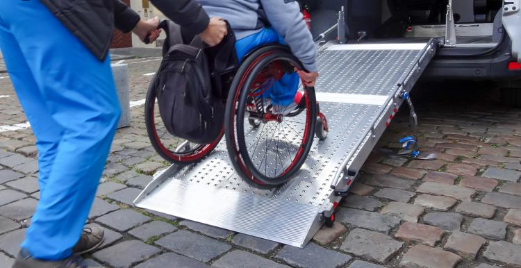Assistant helping disabled person on wheelchair with transport using accessible van ramp