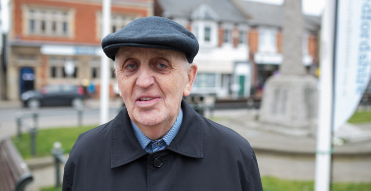 Elderly man wearing a cap standing outdoors