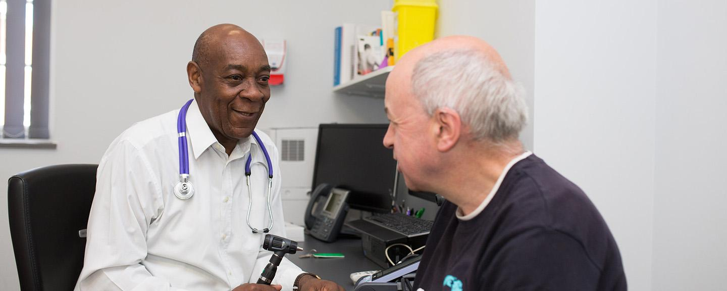 GP holding ear inspection device with patient