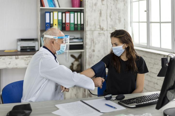 Doctor wearing PPE (personal protective equipment) measures a young woman's blood pressure