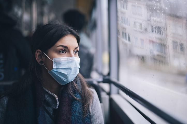 Woman on a bus in a facemask