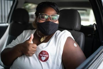Portrait of a happy woman in a car with a 'get vaccinated' sticker - wearing face mask