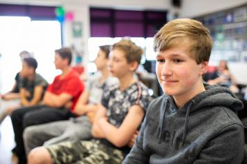 Thoughtful teenage boy in a group setting