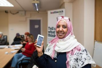Woman in headscarf holding up a smartphone