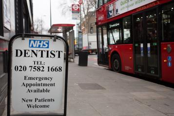 Pre-pandemic photo showing London street with bus stop and NHS dentist sign