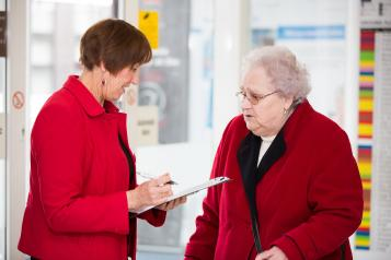 elderly woman in conversation with another woman
