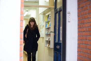 woman walking through the entrance of a GP surgery