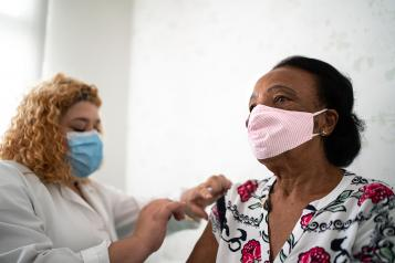 Black woman in a facemask having her flu jab