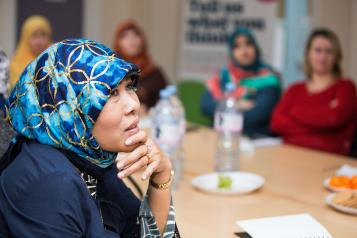 A woman in a headscarf listening