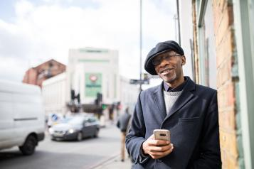 Smiling man standing next to a busy road