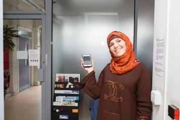 Smiling lady in a headscarf holding up a smartphone