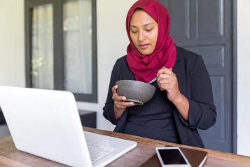Muslim woman with a laptop eating healthily