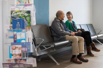 Older man talking to younger woman in a hospital waiting area
