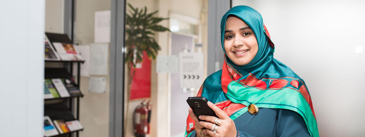 woman in headscarf smiling using a smartphone