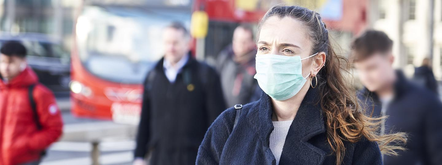 young woman wearing a facemask on a busy London street