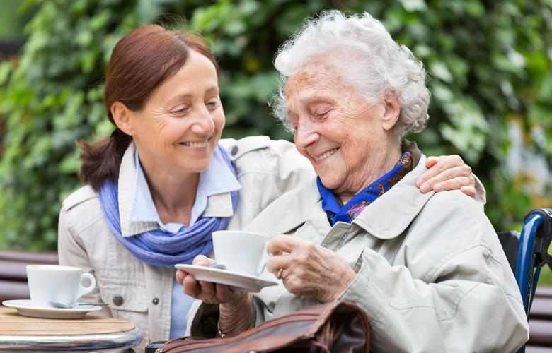 Smiling middle aged woman caring for her mother