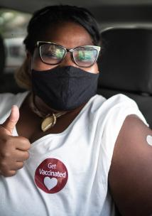 Portrait of a happy woman in a car with a 'get vaccinated' sticker